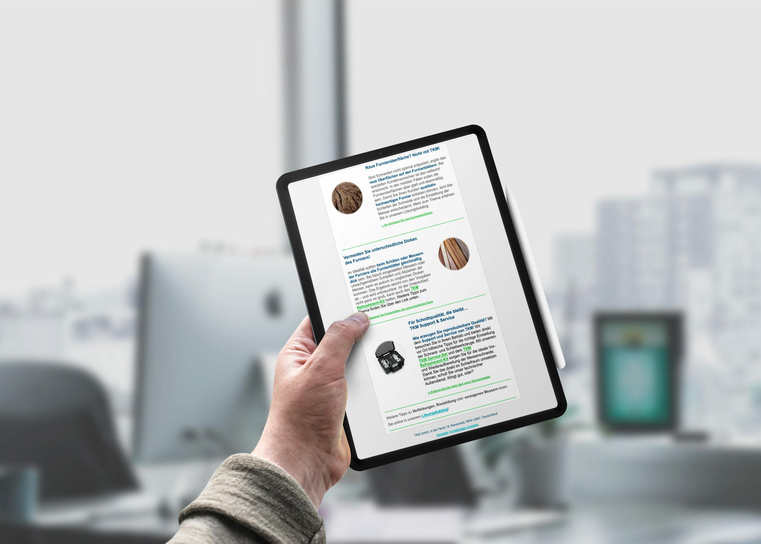 Tablet in Hand zeigt Newsletter von TKM
